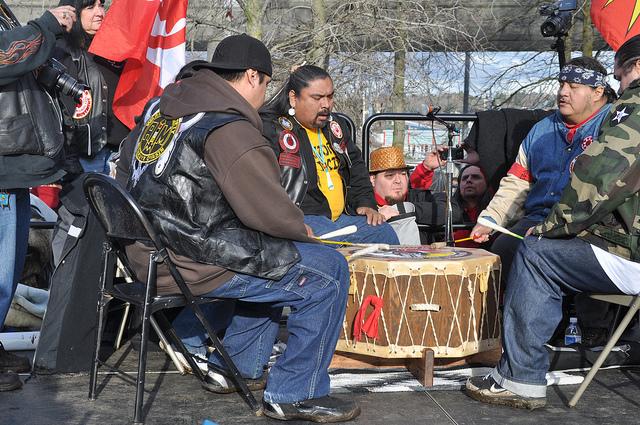 Three members of Warrior Society Mitakuye Oyasin sitting in chairs around a drum, drumming and singing.