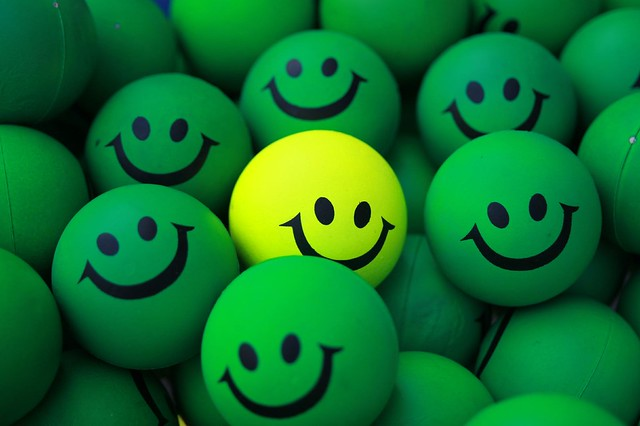 Photo of green circles with smiley faces and one yellow circle with a smiley face