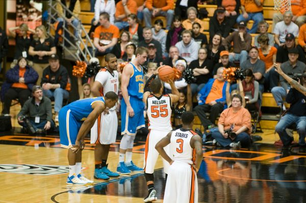 College basketball player shooting a foul shot while fans look on.