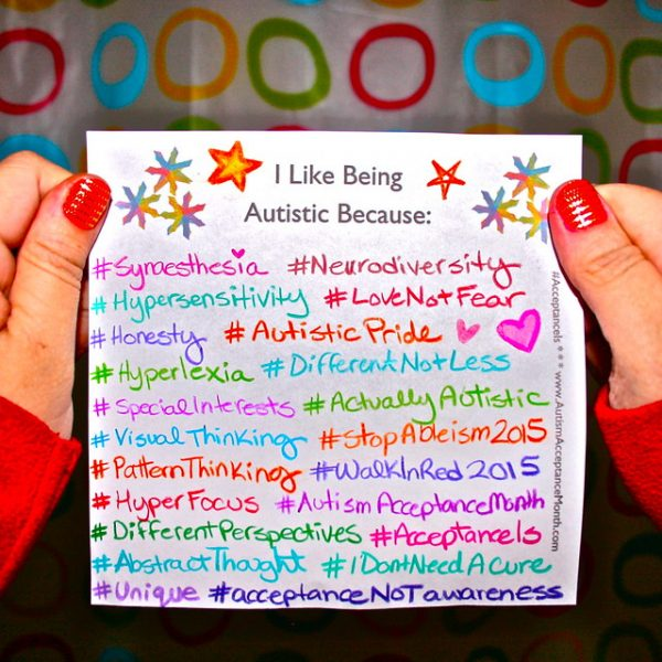 """Photo of two hands holding a paper that says """"I Like Being Autistic Because"""""""