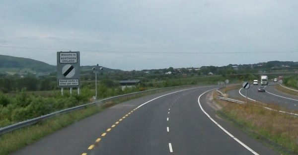 Photo of a highway with a sign by the side of the road that says, welcome to northern ireland